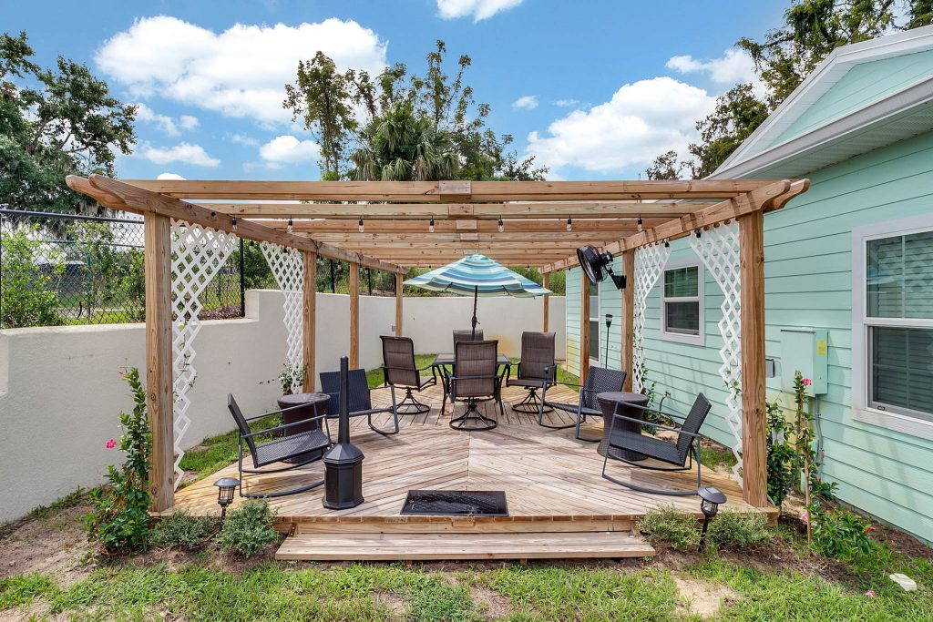 pergola area of Clermont cabanas with raised wood deck, rocking chairs, umbrella shade and table with chaors