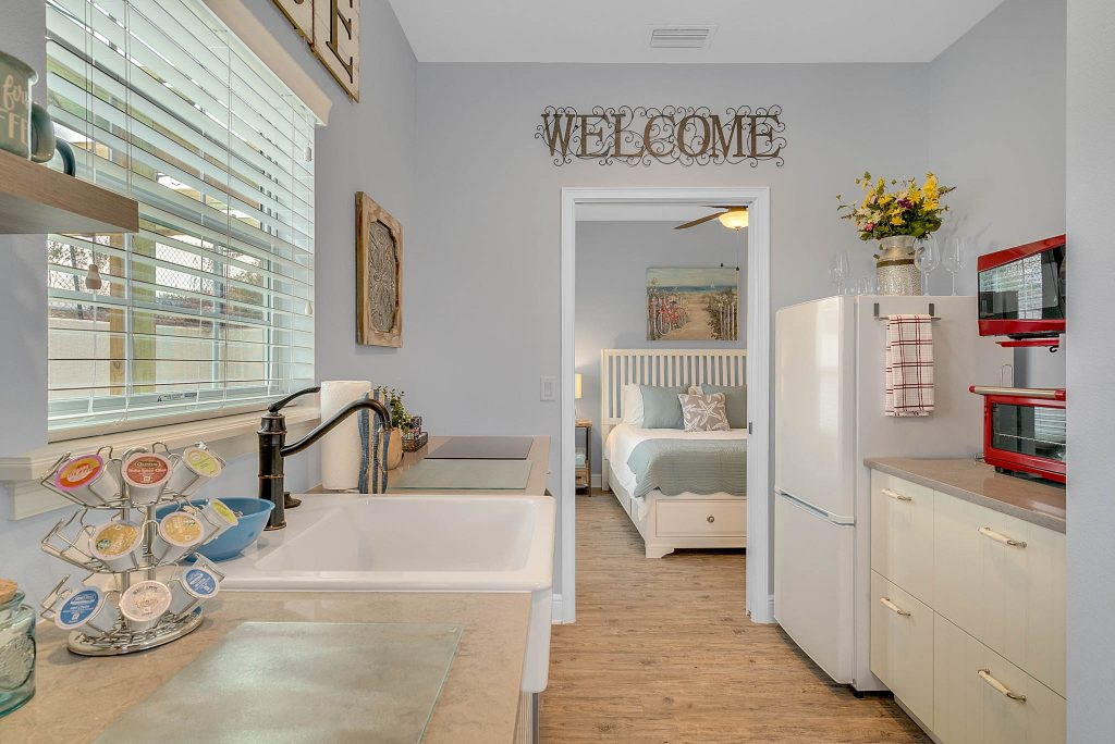 Welcome sign in full kitchen with stocked coffee, refrigerator, appliances, and granite countertop and partial view of bedroom