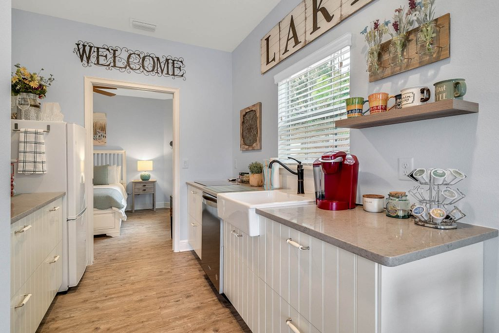 welcome sign in full kitchen with granite countertops and red appliances at Clermont Cabanas in Clermont Florida